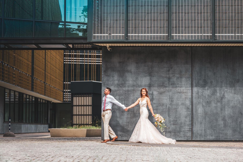 Pruut ja peigmees käest kinni seina ääres pulmapildid ja videograaf pulma