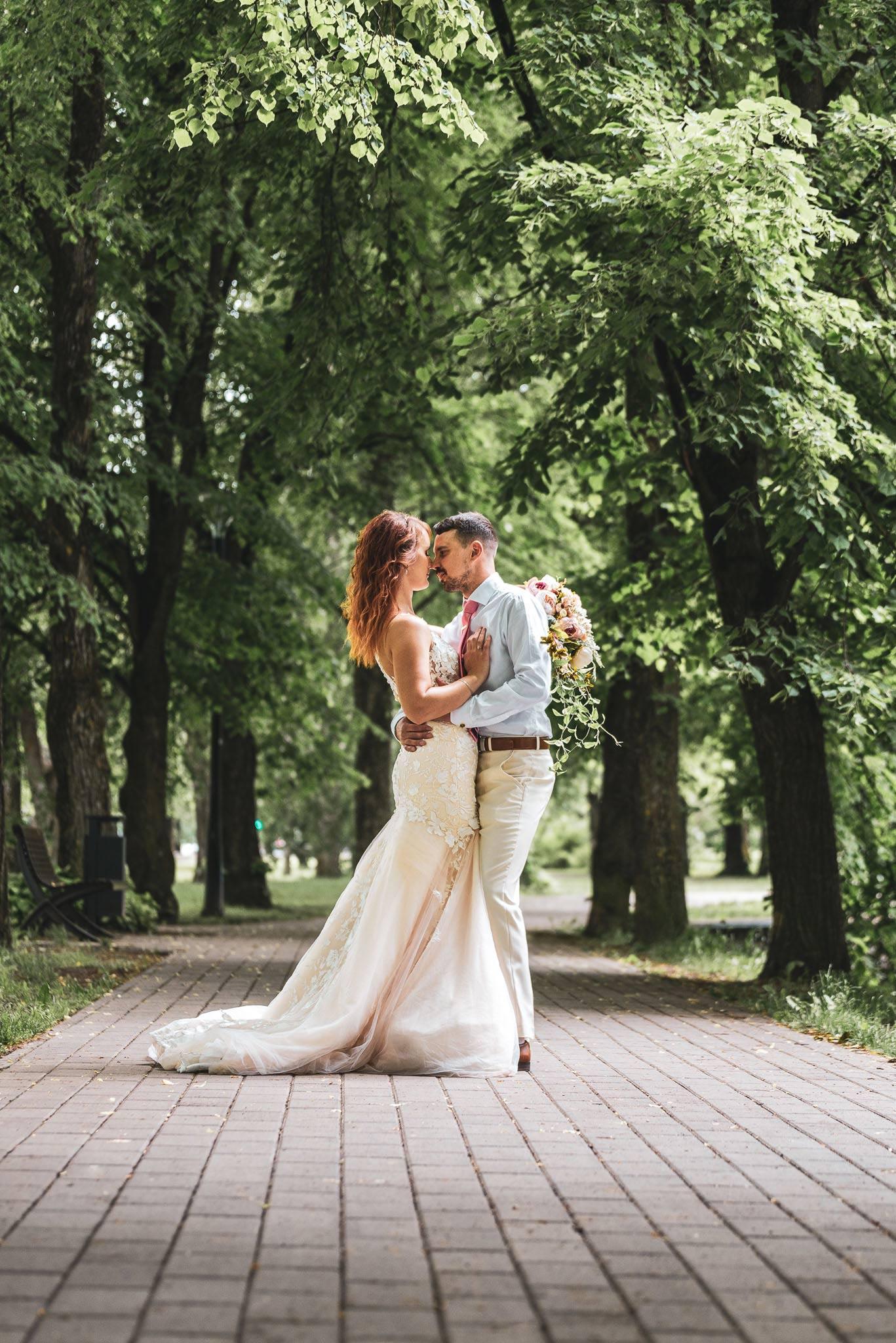 Pruut ja peig Tartus allee vahel pulmafotograaf ja pulmavideo